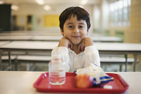 A child sitting in a school cafeteria