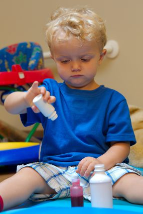 young child playing with medication bottles