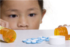child looking at medicine on counter