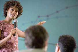 woman holding a microphone speaking to a group
