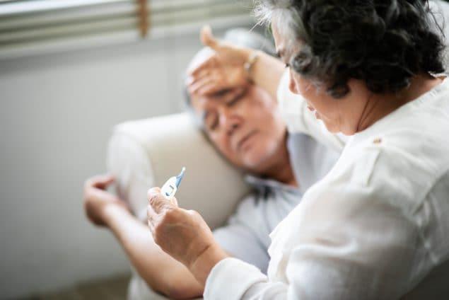 Hombre mayor asiático recostado en un sofá mientras su esposa sostiene un termómetro