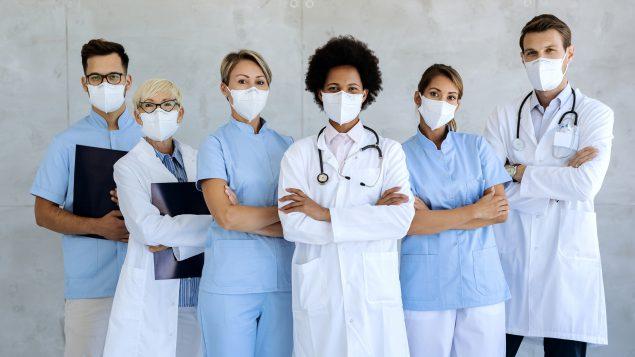 Equipo de expertos médicos con mascarillas que les dan seguridad