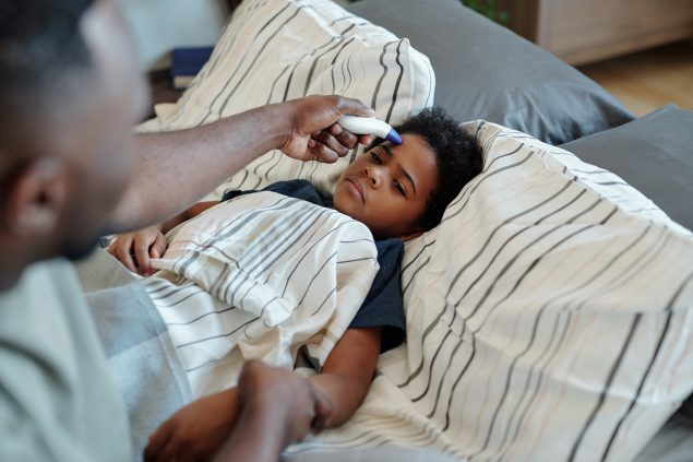 Niño enfermo en cama mirando a su padre...