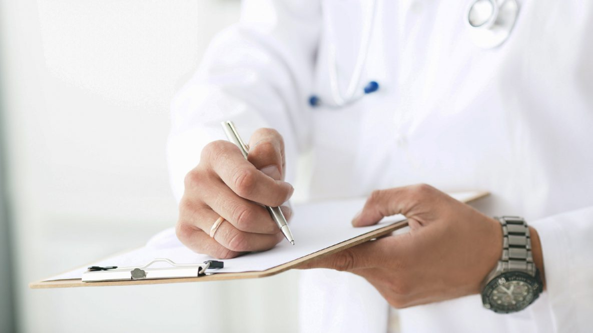 The figure is a photograph of a health care provider writing a prescription for a patient.