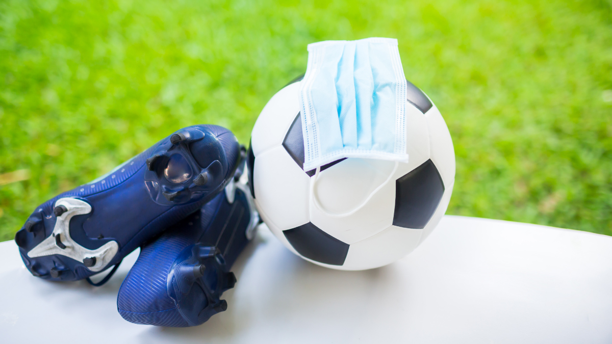 The figure is a photo of soccer cleats and a mask on a soccer ball near a field.