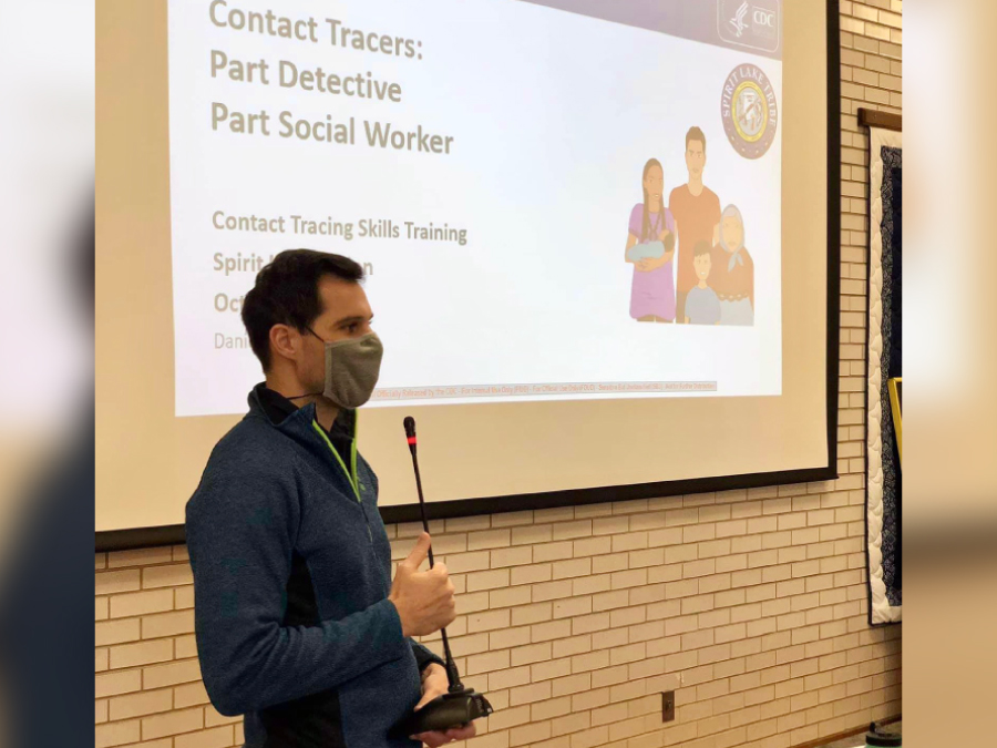 The figure is a photo of a man wearing a mask giving a presentation on contact tracing.