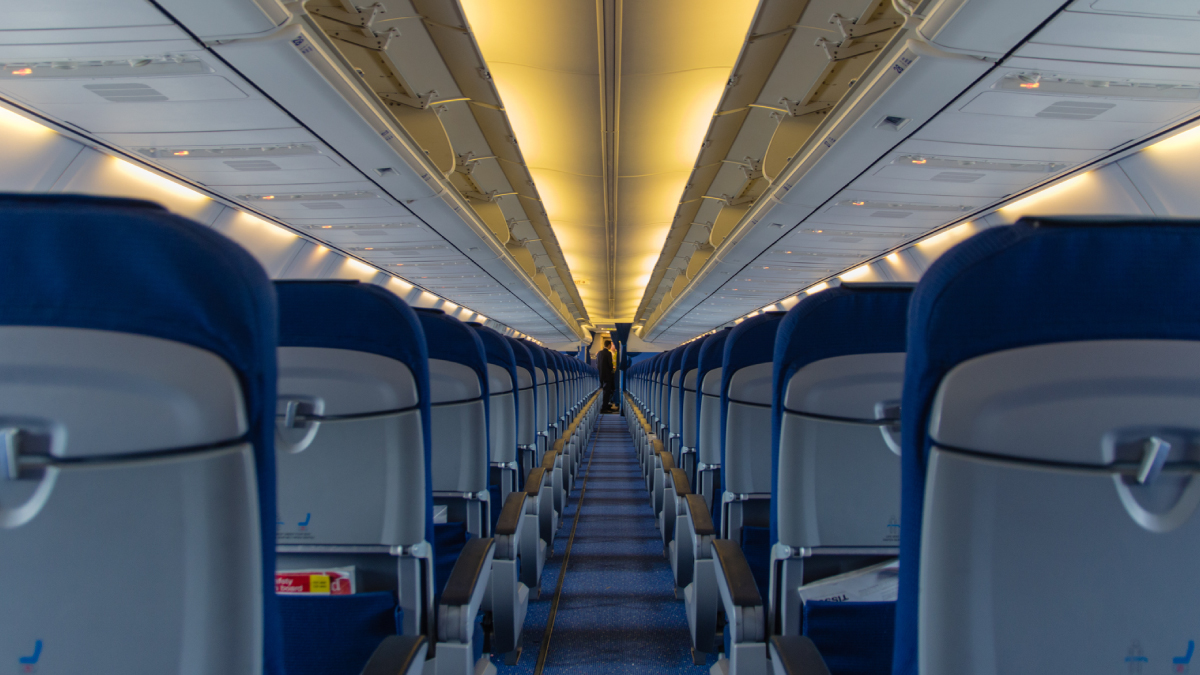 The figure is a photograph of an airplane aisle with empty seats.
