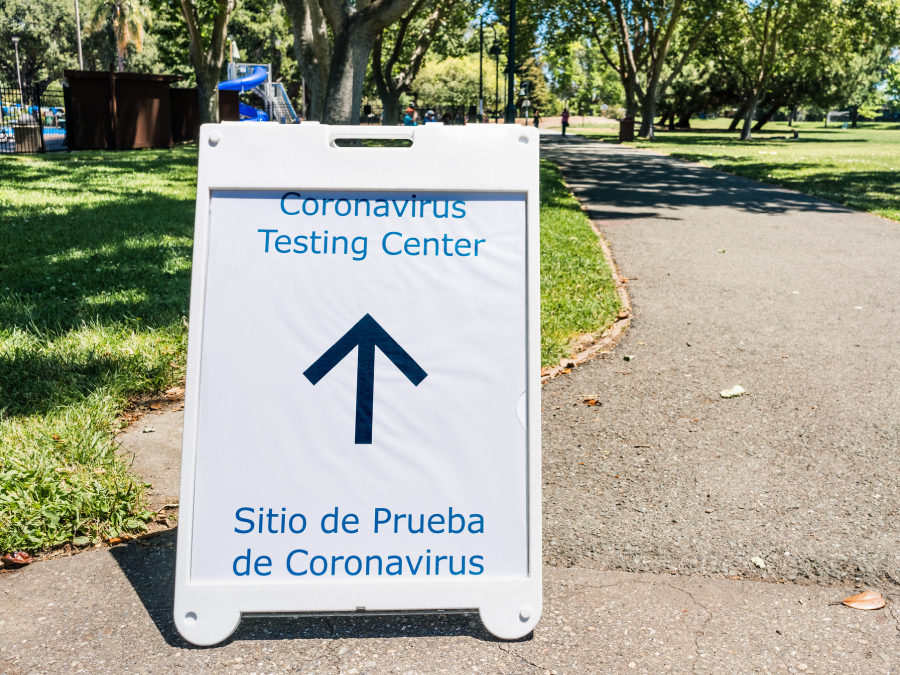 The figure is a photo of a sign for a coronavirus testing center in both English and Spanish.