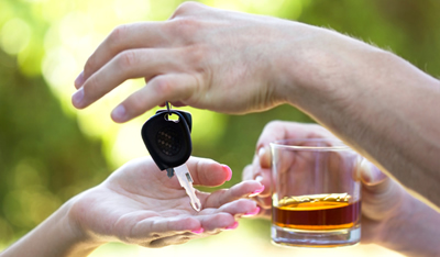 photo: man holding a drink handing over his car keys