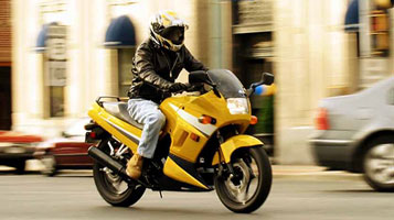 photo: man riding a yellow motorcycle on an urban road