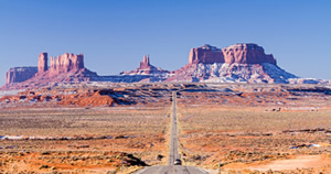 photo: car on a highway approaching Monument Valley