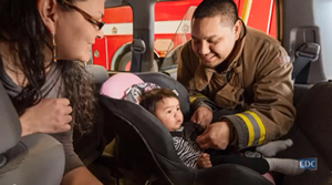 photo: fireman helping Native American mother with her child's car seat.