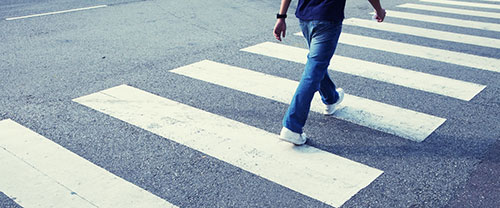 Photo: man in jeans walking across a zebra crossing