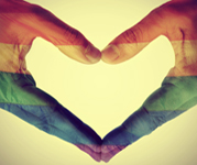 Two hands forming a heart shape, filled with rainbow-colored stripes