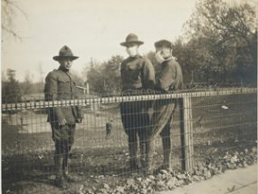 antique photo of soldiers beside a low fence