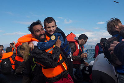 Photo: Greece, 2015: Kinan Kadouni, laughs with the Syrian boy he is carrying ashore near the village of Skala.
