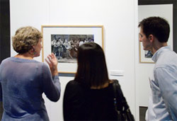 Visitors discuss a photograph in the David J. Sencer CDC Museum's Temporary Gallery.