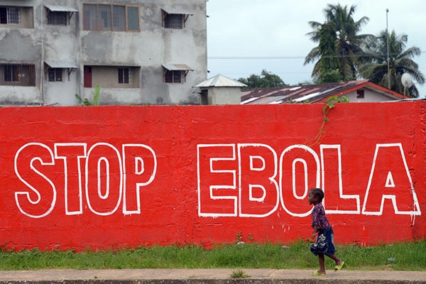 A child in Liberia walks by a Red Sign that says