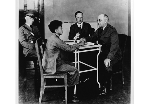 National Library of Medicine; photograph by P.E. Brooks - U.S. Public Health Service (PHS) and Immigration Service officers interrogating a Chinese immigrant, Angel Island, California, 1923 - Asian immigrants who arrived the first part of the 20th century received special scrutiny because they were considered disease carriers. The Asian community mounted many legal challenges to these practices.