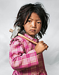 Photograph of a Nepalese child holding a hammer