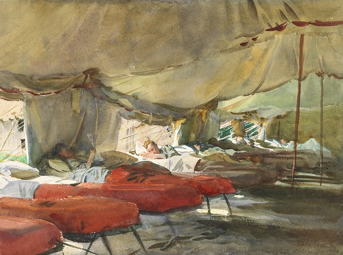 Men in cots in a tent