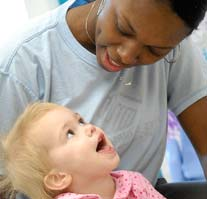 A little girl smiling at her caregiver