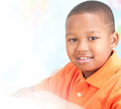A young african american boy in an orange shirt