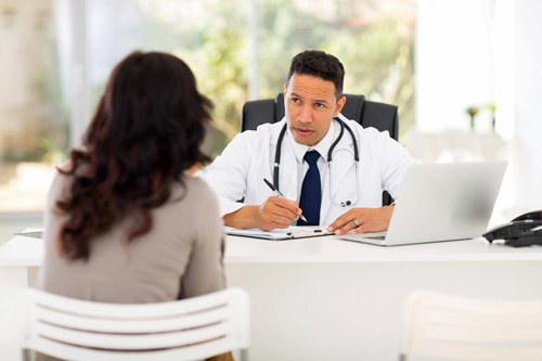 Doctor at his desk talking to a woman