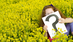 Girl siting in a meadow holding a sign with a question mark on it.