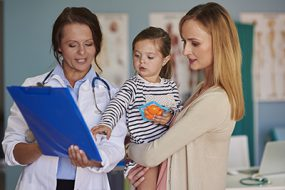 Woman doctor talking with her two patients
