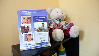 Act Early Materials on a shelf with a teddy bear and toys