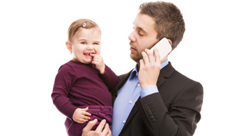 Man talking on phone holding baby.