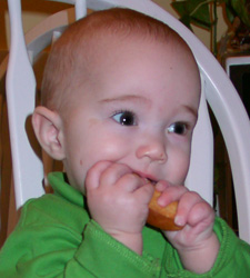Photo: A little boy putting a snack in his mouth with his hands