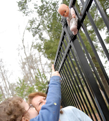 Photo: A little boy has found something in the fence