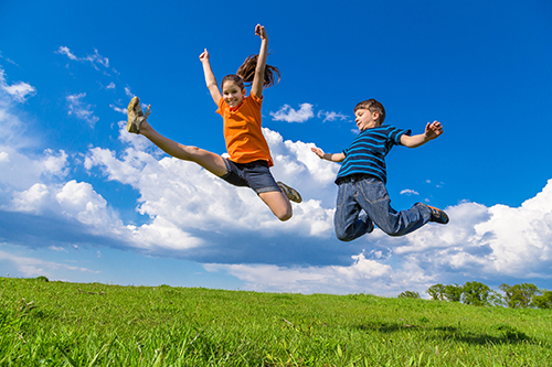 Two children jumping on green hills