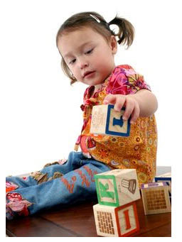 A young girl playing with blocks.