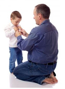 Photo: man helping child with buttons on shirt
