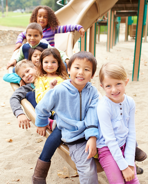 Diverse smiling kids together on a slide at a playground