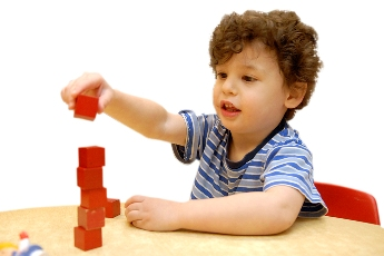 Photo: Child playing with blocks at table