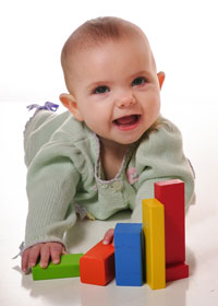 Baby with big smile with blocks
