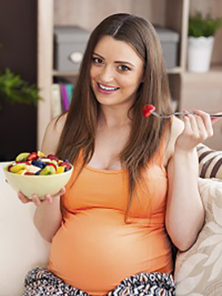 Pregnant woman eating fruit salad