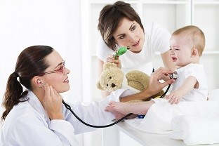 Pediatrician with mother examining baby