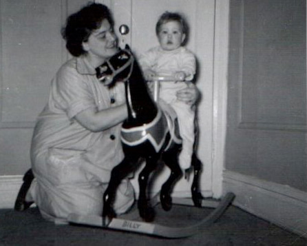William with his mom as a child on a hobby horse