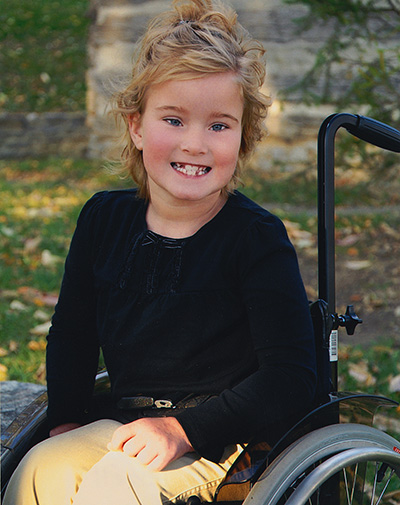 Elley smiling, sitting in a wheelchair.