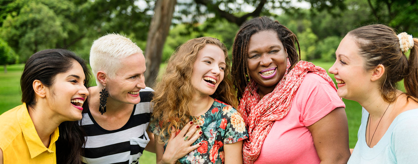 Diverse women smiling and socializing in nature