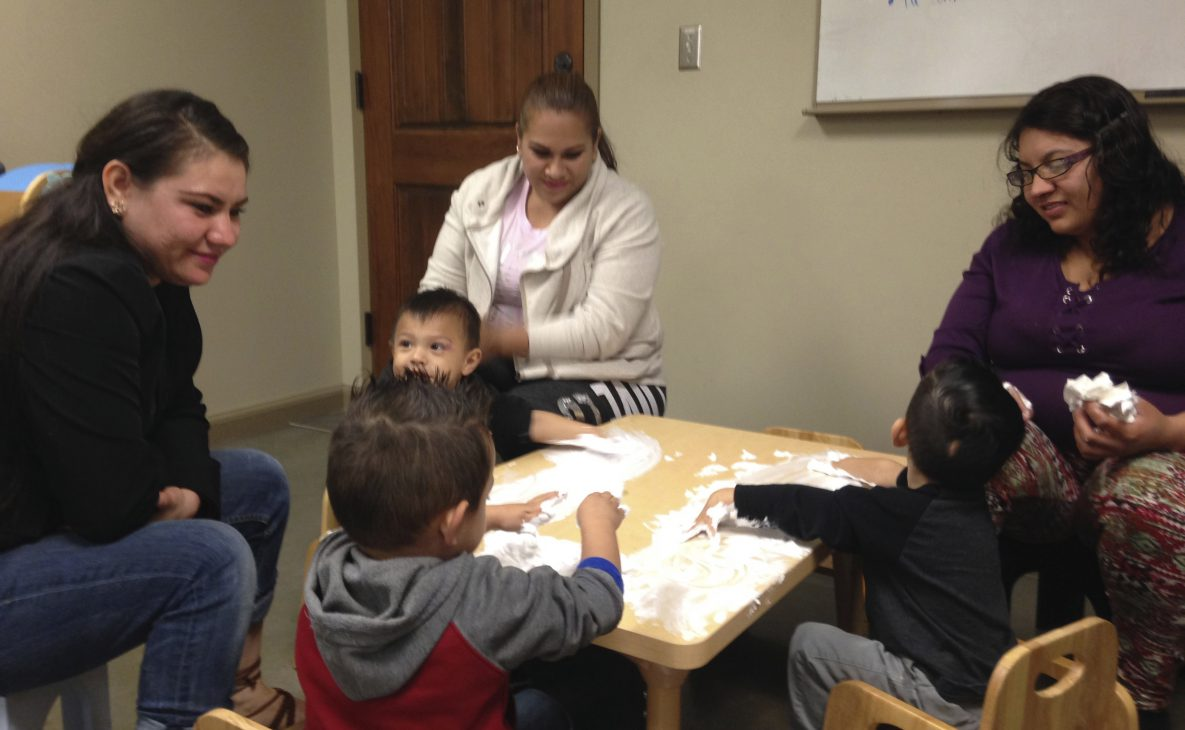 Legacy mothers talking with their children during creative play with shaving cream.