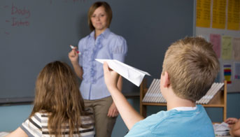 Boy throwing a paper airplane in a classroom