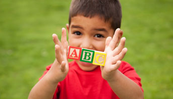 Boy holding A, B, and C toy blocks