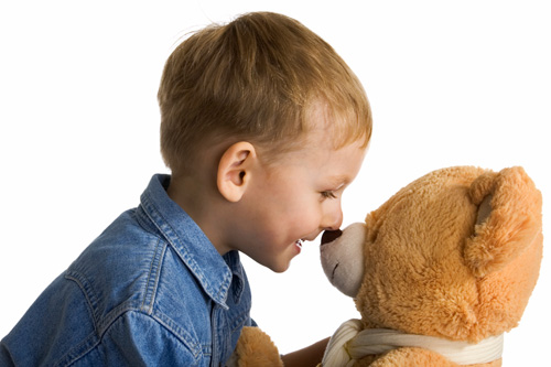 Boy rubbing noses with his teddy bear.