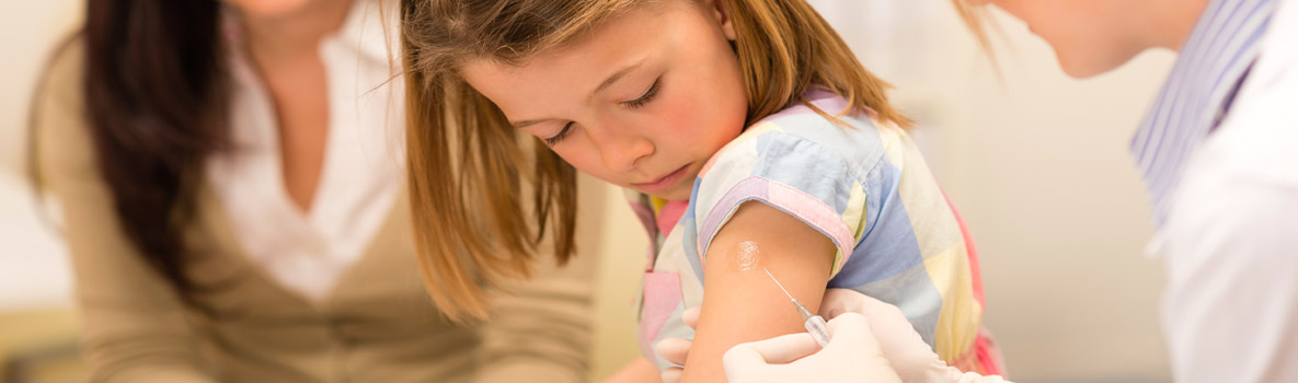 Elementary school girl getting a flu shot.